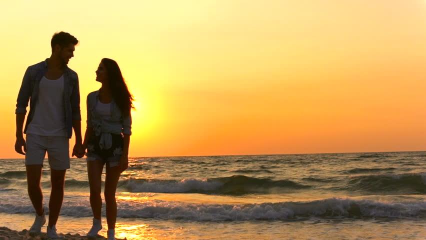 A romantic couple walk on the beach.